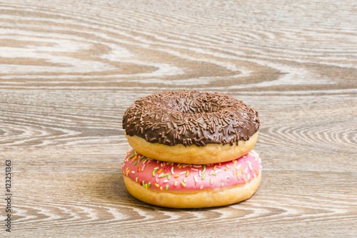 Poster colorful donuts on a wooden background