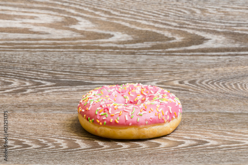 Poster strawberry donut on a wooden background