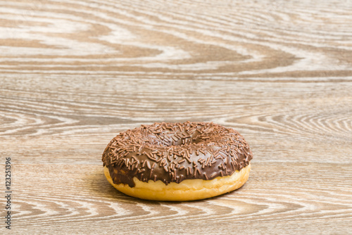 Poster Chocolate donut on a wooden background