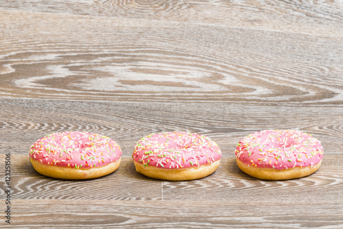 Poster strawberry donuts, isolated on a wooden background