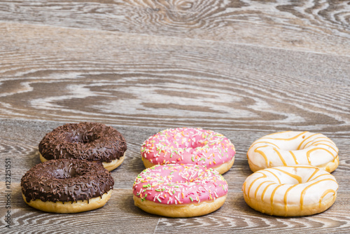 Poster Hand decorated donuts on a wooden background
