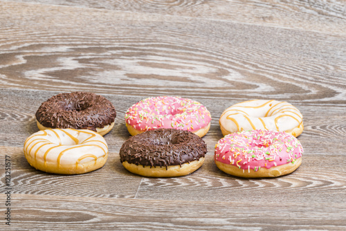 Poster colorful donuts, isolated on a wooden background