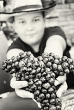 Young funny boy posing with bunch of grapes in hands