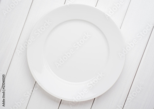 Poster White table setting from above. Empty plate on planked wood .