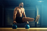 Young man is training by kettlebell.