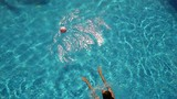 Young woman playing with ball on swimming pool