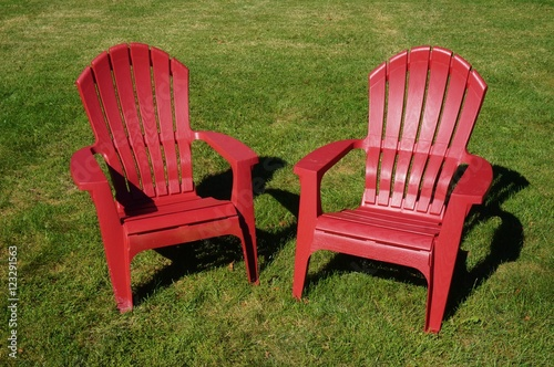 Two Red Adirondack Chairs In The Grass