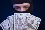 Robber holding money isolated on dark blue