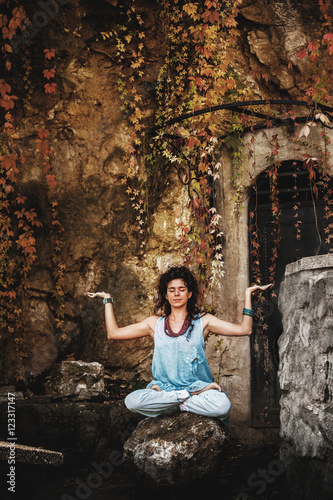 woman practice yoga on rock