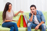 Young couple is sitting at sofa at home. Man is getting bored of talking about shopping.