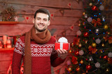 happy man in warm clothes with gift box at home