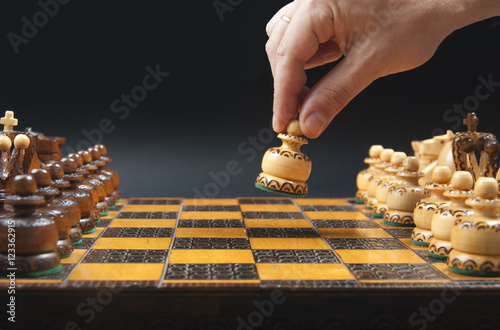Poster Male hand moving white pawn at the beginning of chess game.