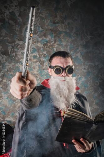 Poster evil wizard Merlin conjures and casts a spell, raising his wand, a young man dre