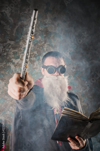 evil wizard Merlin conjures and casts a spell, raising his wand, a young man dre Poster