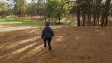 Little boy running in a forest at autumn day