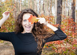 pretty woman with oak leaves in forest