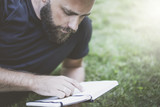 Summer day. Front view of a young bearded man, wearing a black T-shirt, lying on the lawn and reading a book.Selective focus, film effect, blurred background.