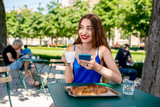 Beautiful woman in the blue dress sitting at the cafe with coffee and croissant using mobile phone outdoors at the park.