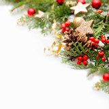 Christmas tree branches with red baubles, golden stars and pine