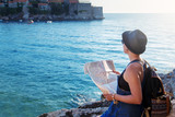 Woman traveler with map with map near sea