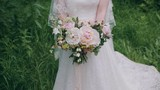 Bride in traditional white wedding dress with flower posy luxury home