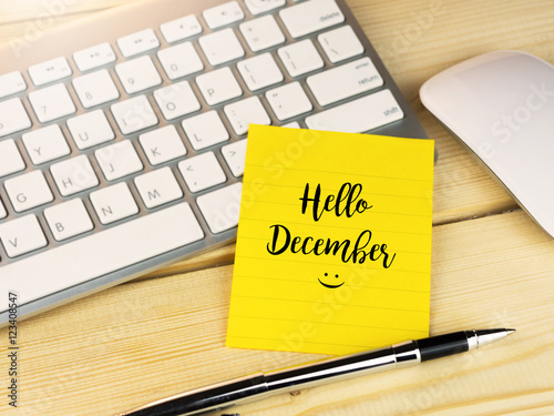 Poster Hello December on sticky note on work table