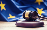 Judges wooden gavel with EU flag in the background. Symbol for jurisdiction. - 123409381