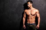 Fototapety Portrait of strong healthy handsome Athletic Man Fitness Model posing near dark gray wall