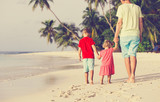 father and two kids walking on summer beach