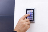 Man dialing pass code on intercom security keypad to open entrance door of the apartment building.