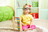 child girl weared glasses playing with abacus toy indoor