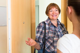 Cheerful greeting of two women at the door - 123456342