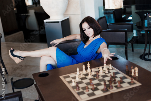 Poster young beautiful woman playing chess