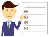 スーツを着た男性が記入済みのチェックリストを指差ししている - 123469369