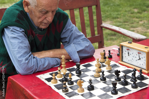 Fotografiet Old man  contemplating and playing chess