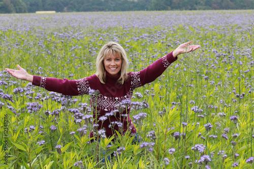 Hübsche Frau mit ausgebreiteten Armen in blauem Blumenfeld