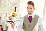 Waiter holding bottle of wine and glasses