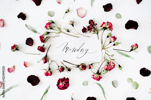 word monday written in calligraphy style on paper with pink, red roses, eucalyptus and leaves on white background. Flat lay, top view