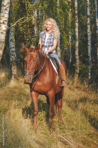 Beautiful young woman riding a horse Poster