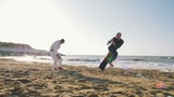 Two male karate fighters posing on stones sea background, slow motion