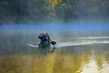 Mother and daughter canoeing in morning mist, North Carolina