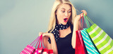 Fototapety Happy young blonde woman with shopping bags