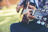 Close up of young hipster man practiced guitar in the park,happy