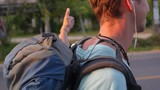 Young Tourist with Backpack Hitchhiking along a Road in Sunset