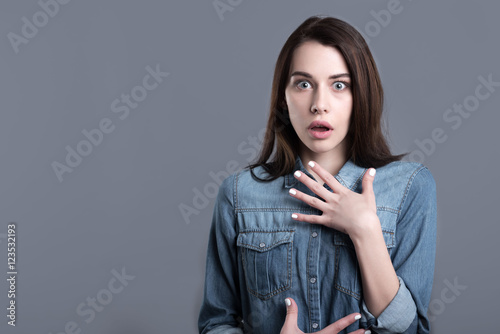 Confused and surprised young woman opening mouth