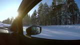 Country road in Finland. Winter. Snow-covered forest. Blue sky and sun. The view from the passenger seat