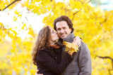 Happy couple kissing in autumn park with yellow trees