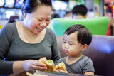 Mother and little boy enjoy eat hamburger