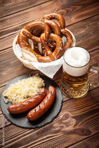 Poster Pretzels, bratwurst and sauerkraut on wooden table