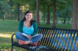 Smiling female college student reading a book on a bench in a park